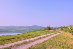 Czech landscape with meadow path leading to new lake named Milada and mountains in spring morning stock photos