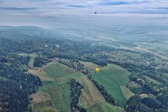 Czech paradise from the hot air balloon. Foggy autumn scenery of the Czech forests with pair of balloons Royalty Free Stock Photo