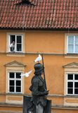 Czech, Prague: A man feeds gulls from the window of the house royalty free stock photo