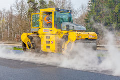 CZECH REPUBLIC, PLZEN, 7 MAY, 2016:Asphalt spreading machine and vibration roller  at pavement road works. Stock Photos