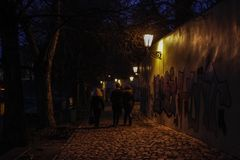 Night pedestrian road in Prague illuminated by a lamp and graffiti on the wall royalty free stock photography