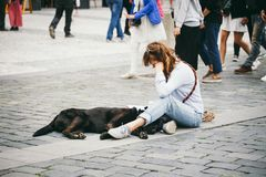 Czech Republic, Prague, July 25, 2017: A beautiful young woman painter sits on the floor in the middle of the square and draws, be royalty free stock photo