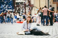 Czech Republic, Prague, July 25, 2017: A beautiful young woman painter sits on the floor in the middle of the square and draws, be Stock Images