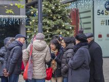 Czech republic, Prague, old town, December 6, 2017: group of tou. Rist standing and talking in front of decorated christmas tree in old prague center narodni Stock Images