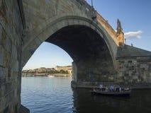 Czech Republic, Prague, September 8, 2018: Boat with tourist peoples sailing under Charles bridge arc on Vltava river, golden hour stock photography