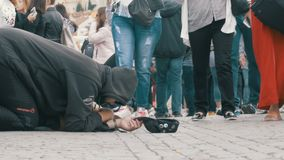 Homeless Beggar Man with a Hat on the Sidewalk Begs for Alms from People Passing by. CZECH REPUBLIC, PRAGUE, SEPTEMBER 12, 2017: Homeless Beggar Man with a Hat stock footage