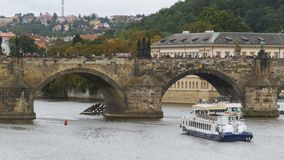 Landscape view of Prague Bridge and Water Bus Boat Floating on the River Vltava. CZECH REPUBLIC, PRAGUE, SEPTEMBER 12, 2017: Landscape view of Prague Bridge and