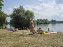 Czech Republic, Probostska jezera, August 8, 2018: People rest on the shore of a pond, bathing and swiming, grass and trees, blue. Sky summer day royalty free stock photography