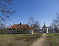 Czech Republic, Skalka, April 7, 2018: baroque monastery Skalka. With small chapel in sunny day early spring, grass, bare tree and blue sky background Stock Photography