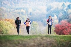 Free CZECH REPUBLIC, SLAPY, October 2018: Trail Maniacs Run. Man Competite With Young Couple. Autumnal Forest On Background. Stock Photos - 129919313