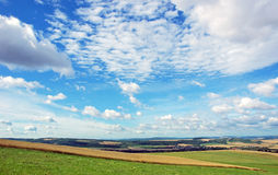 Czech summer landscape. Traditional Bohemian summer landscape with fields and meadows and big blue cloudy sky, Tenovice, Czech Republic Royalty Free Stock Photo