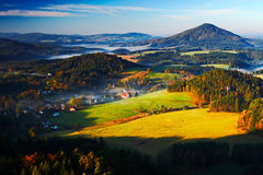 Czech typical autumn landscape. Hills and villages with foggy morning. Morning fall valley of Bohemian Switzerland park. Hills wit Royalty Free Stock Photos