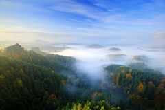 Czech typical morning autumn landscape. Hills and villages with foggy sky. Morning fall valley of Bohemian Switzerland park. Hills Royalty Free Stock Photography