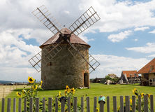 Czech windmill. Windmill behind a wood stockade with cup and sunflowers Stock Images