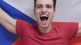 Czech Young Man celebrates holding the flag of Czech Republic in Slow Motion. High quality royalty free stock photos