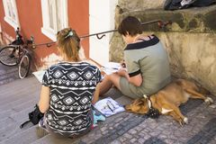 Czechia two women sit and drawing watercolor painting Prague city. With dog sleep on pathway of Prague castle on August 31, 2017 in Prague, Czech Republic stock photo