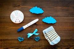 Czekać na dziecka z pozytywnym ciążowym testem, skarpetami i serca drewnianego tła odgórnym widokiem, zdjęcie royalty free