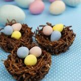 Czekolad gniazdeczka wypełniali z Wielkanocnymi jajkami na błękicie Fotografia Stock