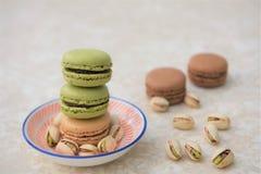 Czekolada i pistacjowi smaku macaroon ciastka z dokrętkami na marmuru stole Zdjęcia Royalty Free
