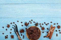 Czekolada, wanilia wtyka, cynamon, kawowe fasole na błękitnym drewnianym tle z kopii przestrzenią dla twój teksta Odgórny widok obraz stock