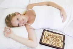 czekoladki łóżkowe leży kobieta w ciąży Obrazy Royalty Free