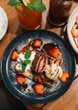Czekoladowa gofr polewa z miarką waniliowy i truskawkowy lody, bat śmietanka, pokrojona truskawka Obraz Stock