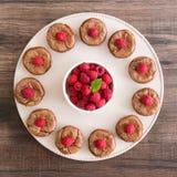 Czekoladowa lawa zasycha z świeżymi rspberries i nowym liściem układającymi w okręgu na porcelan talerzu Fotografia Stock