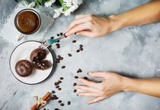 Czekoladowe babeczki z filiżanką gorąca czarna kawa na cocrete tle Kobiet ręki cią babeczkę Obrazy Royalty Free