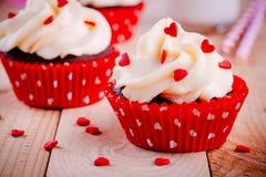 Czekoladowe babeczki z waniliową śmietanką i czerwieni cukrowymi sercami dla walentynka dnia zdjęcie royalty free