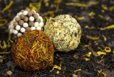 Czekoladowe piłki pokrywać w żółtych kwiatów płatkach, dokrętkach i, confect Zdjęcia Stock