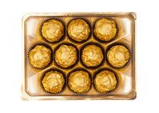 Czekoladowe piłki z migdałem w złocistej folii tapetują na bielu Obraz Royalty Free