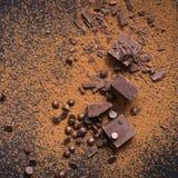czekoladowe tła ciemne deser sweet białe Kawałki i krople czekolada, kakaowy proszek na czerni obraz stock