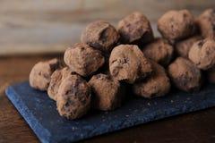 Czekoladowe trufle w kakao kropiącym Na łupkowej desce na drewnianym tle Zakończenie, tekstura zdjęcia stock