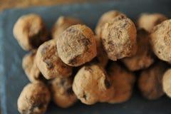 Czekoladowe trufle w kakao kropiącym Na łupkowej desce na drewnianym tle Zakończenie, tekstura obraz stock