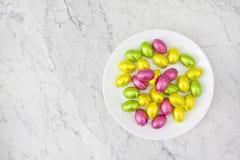 Czekoladowego cukierku złoci jajka na bielu talerzu Wielkanocnego mieszkania nieatutowy stołowy odgórny widok z marmurowym tłem fotografia royalty free