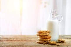 Czekoladowego układu scalonego ciastka, butelka i szkło mleko na drewnianym stołowym pobliskim okno, biały tło Pogodny ranek, kop Fotografia Stock