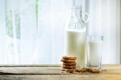 Czekoladowego układu scalonego ciastka, butelka i szkło mleko na drewnianym stołowym pobliskim okno, biały tło Pogodny ranek, kop Zdjęcie Royalty Free