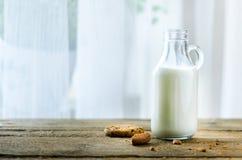 Czekoladowego układu scalonego ciastka, butelka i szkło mleko na drewnianym stołowym pobliskim okno, biały tło Pogodny ranek, kop Zdjęcie Stock