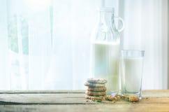 Czekoladowego układu scalonego ciastka, butelka i szkło mleko na drewnianym stołowym pobliskim okno, biały tło Pogodny ranek, kop Obraz Stock