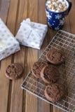 Czekoladowi ciastka przy metalu grillem z pieluchą, filiżanką czekolada i teraźniejszością na drewnianym tle, obraz stock
