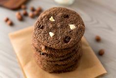 Czekoladowi ciastka z hazelnuts, białą czekoladą i zmrok czekoladą na pergaminie, drewniany tło Obraz Stock