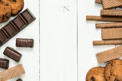 Czekoladowi cukierki, czekoladowe gofr rolki, ciastka na drewnianym bielu stole, przestrzeń w centrum dla teksta obrazy stock