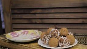 Czekoladowi cukierki i herbaciany ustawiaj?cy na drewnianym stole Porcelany herbaciany ustawiający na woodan tle zbiory wideo