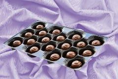 Czekoladowi cukierki w brązie boksują nad jedwabniczym tłem Zdjęcia Stock