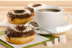 Czekoladowi donuts z kawą i cukierem na drewnianym stole Obraz Stock