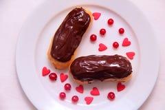 Czekoladowi eclairs na talerzu na białym tle kropiącym z czerwonego rodzynku sercami i jagodami Zdjęcia Royalty Free
