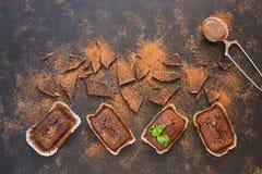 Czekoladowi muffins z czekoladowymi plasterkami kropiącymi z kakaowym proszkiem na ciemnym tle, odgórny widok zdjęcie royalty free