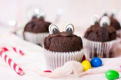Czekoladowi muffins z jadalnymi oczami i kolorowymi bonbons Obrazy Royalty Free
