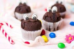 Czekoladowi muffins z jadalnymi oczami i kolorowymi bonbons Fotografia Royalty Free