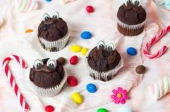 Czekoladowi muffins z jadalnymi oczami i kolorowymi bonbons Obraz Royalty Free
